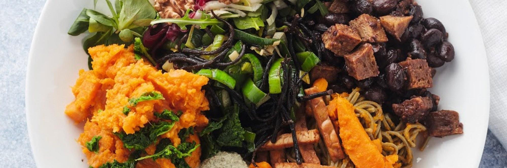 Cashewkaaskroketjes met een spinazieslaatje en tamari-amandelen
